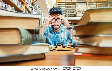 Concentrated Bearded Student Wears Glassses At The Table With Books In The Library Reading Hall
