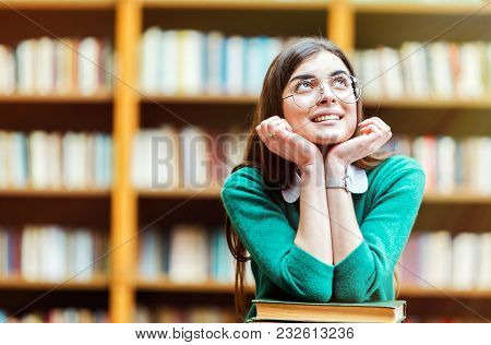 Portrait Of Brunette Girl Student With Stack Of Books In The University Library