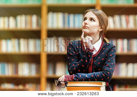 Portrait Of Blonde Girl Student Holding Stack Of Books In The University Library