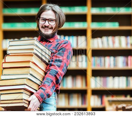 Bearded Student Man With Glasses Holds Stack Of Books Near Bookshelf In The Library