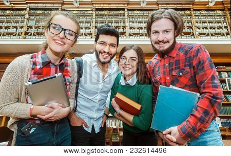 Group Of Smiling Students, Two Young Men And Women Standing Before Library Bookshelves, Holding Book
