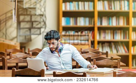 Concentrated Bearded Man Studying With Books And Laptop In The University Library