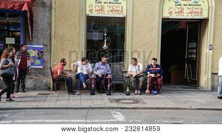 Munich Germany -september 8, 2017; Middle Eastern Men In Munich Side Street Sitting Outside Shop On