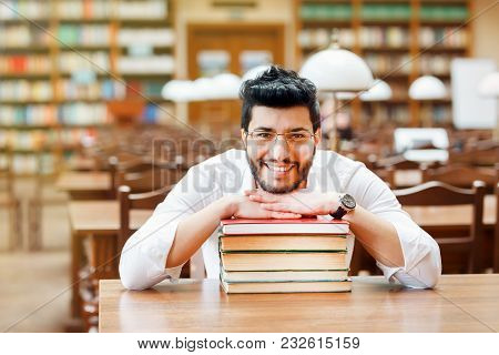 Portrait Of Young Smiling Bearded Man Student With Stack Of Books Before Bookshelves In The Library