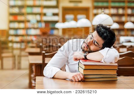 Portrait Of Young Sleeping Bearded Man Student With Stack Of Books On The Table Before Bookshelves I
