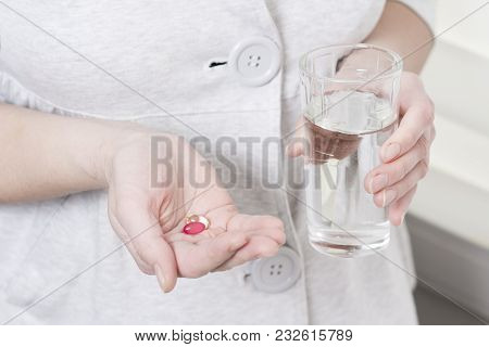 Pills Medication And Glass Of Pure Water In The Hands Of Girl. The Concept Of Drug Treatment. A Woma