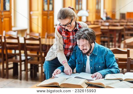 Two Smart Students Working On Home Assignment, Reading Books Attentively, Sitting At Square Library