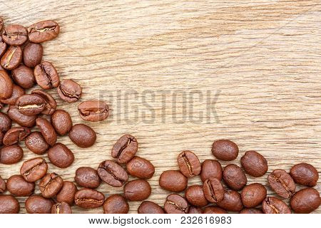 Coffee Beans On Wood Texture Background. High Resolution Photo.