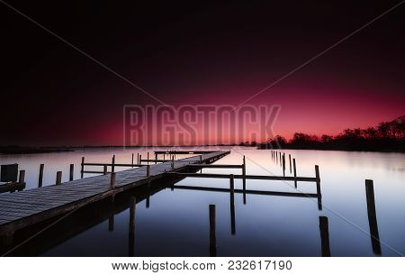 Wooden Platform Before Dawn In A Calm Lake Under A Red Sky