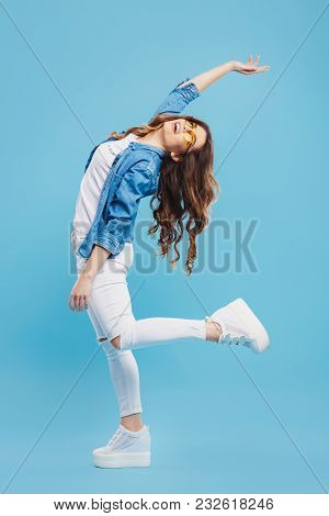 Attractive Young Woman Posing On Blue Background. Pretty Girl Having Fun