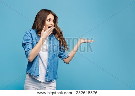 Beautiful Young Woman In Yellow Sweater Posing On Blue Background. Attractive Woman Pointing Fingers