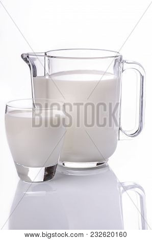 A Jug And A Glass Full Of Fresh Milk On A White Background