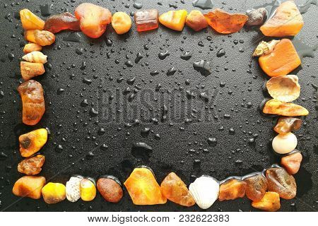 Frame Made Of Natural Amber On A Dark Background With Rain Drops.