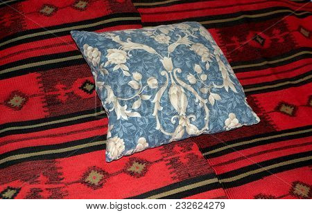 The Sofa Is Covered With A Red Blanket.on Top Is A Blue Cushion.