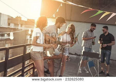 Friends Having Fun At Rooftop Party, Playing The Guitar And Singing. Focus On The Guy Playing The Gu