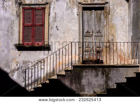 Traditional Sun-lit Rustic Italian Architecture Facade With Stairs Alongside Iron Railing Leading To