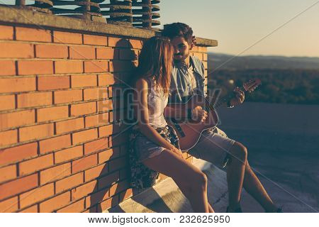 Couple In Love Hanging Out At A Rooftop Party, Leaning Against A Brick Wall ; Guy Playing The Guitar