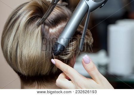 Hairdresser Makes Hairstyle Girl With Brown Hair In A Beauty Salon. Create Curls With Curling Irons.