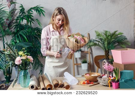 Photo of blonde florist in apron with bouquet with kraft paper on table with paper, marmalade