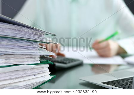 Bookkeeper or financial inspector  making report, calculating or checking balance. Binders with papers closeup. Audit and tax service concept. Green colored image background. poster