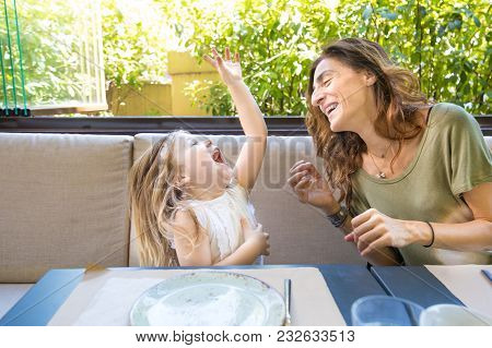 Woman And Girl Laughing Out Loud In Restaurant