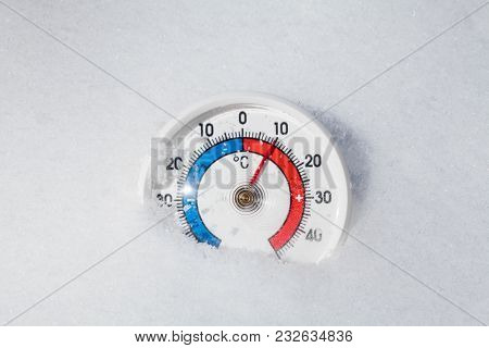 Thermometer with celsius scale in melting snow showing plus 10 degree temperature warm spring weather or global warming concept