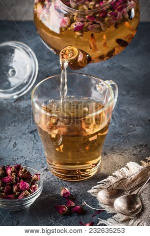 Pouring Tea Into Cup Mug Of Teapot With Detox Drink From Flower Buds Dry Red Pink Rose Tea With Drop