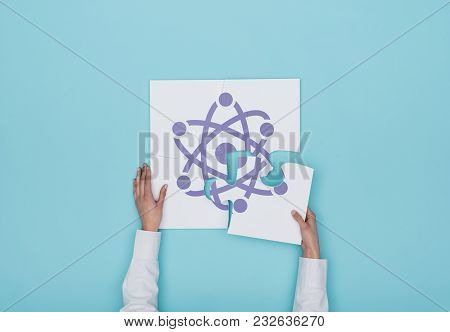 Woman Completing A Puzzle With Atom Icon
