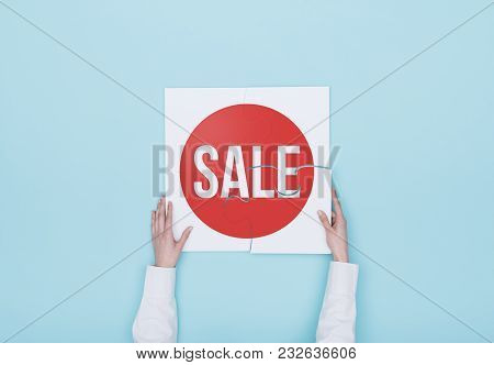 Woman Completing A Puzzle With A Sale Badge