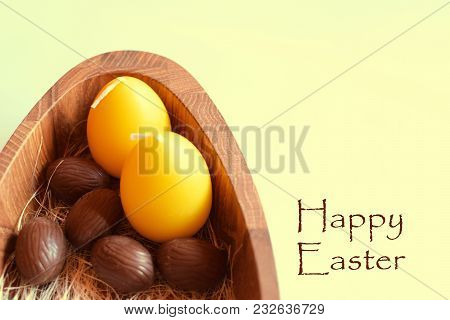 Chocolate Easter Eggs And  Two Yellow Candles In Wooden Plate On Yellow Background As Template For G