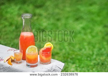 Citrus Cocktail With Ice And Mint In Beautiful Glasses And A Jug, Fresh Ripe Citrus In The Garden. G
