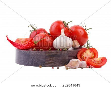 Composition Of Tomato Bunch And Chili Pepper And Garlic On A Wooden Plate