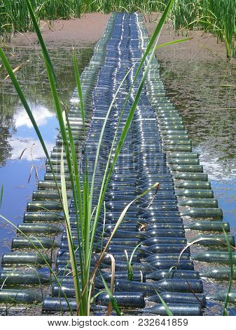 A Bridge Made Of Empty Wine Bottles Stretches Across A Pond. The Pond Is Filled With Reeds. White Cl