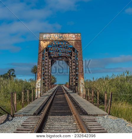 Blue Sky Is The Backdrop For The Iron Train Bridge Passing Through The Reeds Of River Crossing.