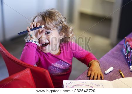 The Small Baby Girl Draws With Felt-tip Pen And