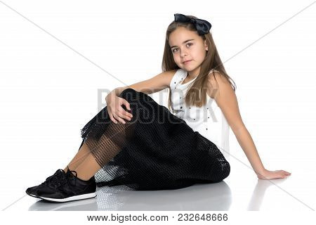 A Beautiful Teen Girl Sits On The Floor On A White Background. The Concept Of Education And Schoo. I