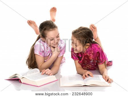 Lovely Little Girls Are Reading A Book. The Concept Of Education And Education, Family And People. I