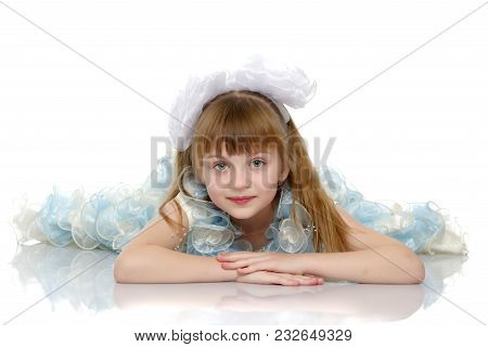 Beautiful Little Girl Lies On The Floor On A White Background. The Concept Of A Happy Childhood, Wel