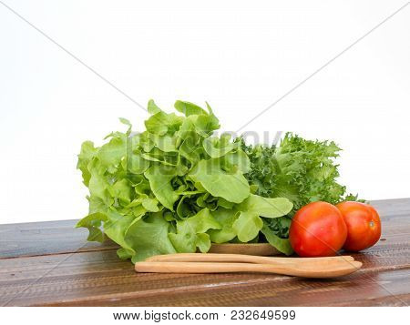 Salad Set Are Tomato, Frilly Iceberg And Green Oak Placing On Wooden Tray With Spoon And Fork On Whi