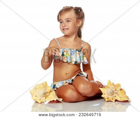 A Little Girl In A Swimsuit With A Shell. The Concept Of A Family Vacation At Sea, A Happy Childhood