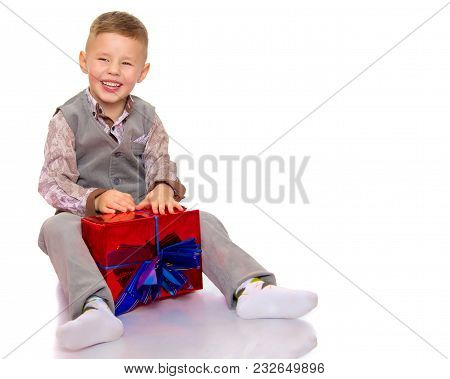 A Happy Little Boy Holds A Beautifully Wrapped Box In Which Lies A Gift. The Concept Of Holidays, Ne