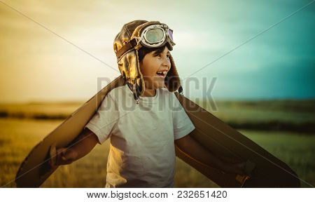 Aviation, Happy child playing with toy wings against summer sky background. Retro vintage toned. Travel and adventure concept