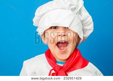 Cooking, The little boy in a suit of the cook. adorable little boy in chef hat and apron smiling at camera in kitchen. boy in chef's hat