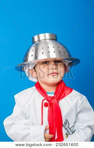 The little boy in a suit of the cook. adorable little boy in chef hat and apron smiling at camera in kitchen. boy in chef's hat