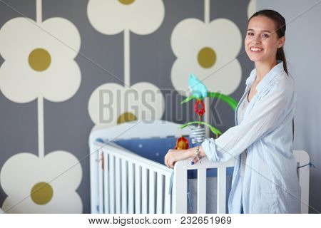 Young beautiful woman standing near children cot