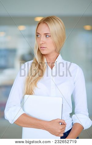 Young businesswoman standing in business center with laptop