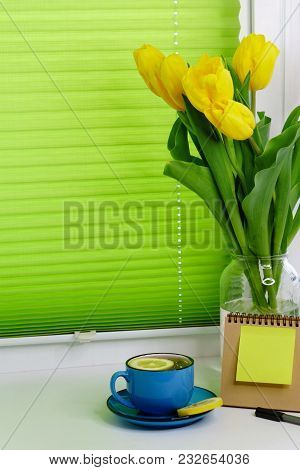 Yellow Tulips In A Jar, Blue Cup With Saucer And Tea With Lemon, Pen, Note Paper And Notepad Stand O