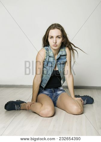 Joyful Smiling Hipster Girl In A Denim Jacket And Shorts Posing On A Light Background.