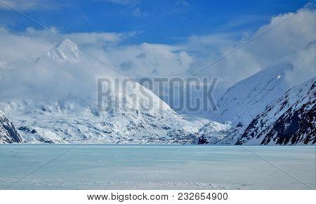 Winter At Portage Glacier Lake.  Frozen Lake, Glacier And Snow Covered Mountains In Alaska