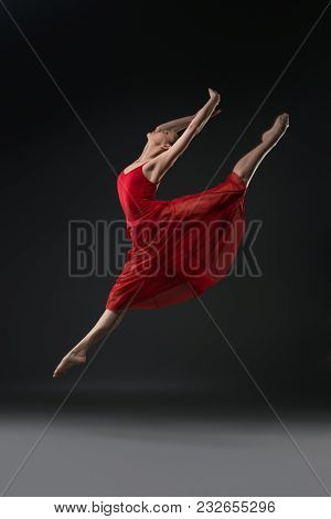 Slim Girl Wearing Red Chiffon Dress Jumping Barefoot Gracefully In The Dark Room